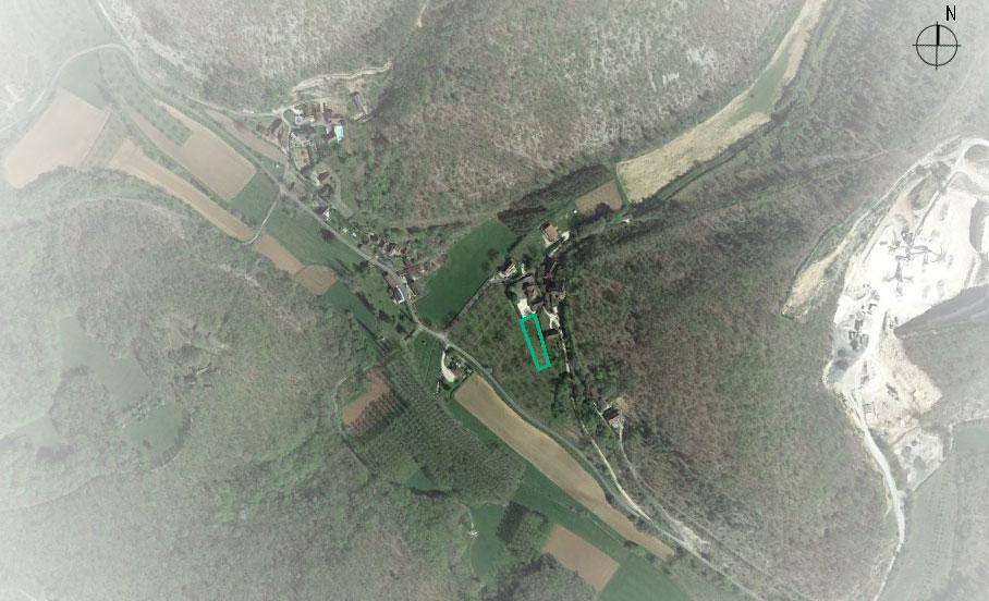 Le terrain est situé dans un petit hameau. Il possède une vue dégagée sur les collines environnantes et présente une légère pente.